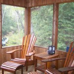 Screened-in sunroom with Muskoka furniture.