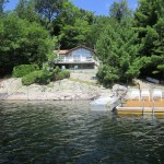 This bright and beautiful 3 bedroom cottage is right on the water with a stunning island vista on prestigious Kennisis Lake.