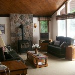 Living room looks out over spacious front deck and lake.