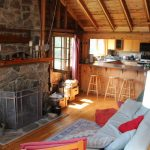Open living room with vaulted pine ceilings and flagstone fireplace