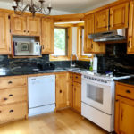 Fully equipped kitchen with granite counters and backsplash