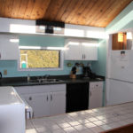 Bright kitchen, elevated pine ceiling. Dishwasher. Bar stools at counter